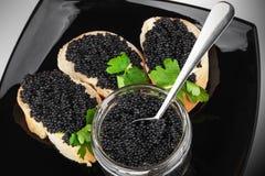 Bocadillos con el caviar negro en la placa Fotografía de archivo libre de regalías