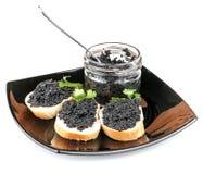 Bocadillos con el caviar negro en la placa aislada Imágenes de archivo libres de regalías