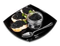 Bocadillos con el caviar negro en la placa oscura Foto de archivo