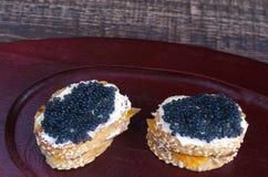Bocadillos con el caviar negro en una bandeja de madera Foto de archivo