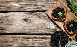 Bocadillos con el caviar negro, un tarro del caviar y la cuchara Fotos de archivo libres de regalías