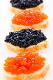 Bocadillos con el caviar negro y rojo Imágenes de archivo libres de regalías