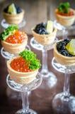 Bocadillos con el caviar negro y rojo Fotos de archivo