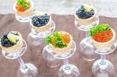 Bocadillos con el caviar negro y rojo Fotos de archivo libres de regalías