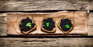 Bocadillos con el caviar negro y verdes Foto de archivo