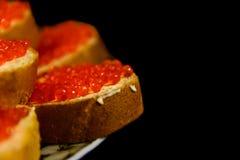 Bocadillos con el caviar rojo aislado en fondo negro Imagenes de archivo