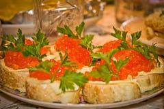 Bocadillos con el caviar rojo en la tabla Imagen de archivo