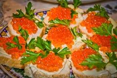Bocadillos con el caviar rojo en la tabla Foto de archivo