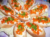 bocadillos con el caviar rojo y las cebollas verdes fotos de archivo