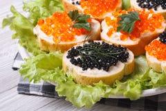 Bocadillos con el caviar rojo y negro de los pescados Imágenes de archivo libres de regalías
