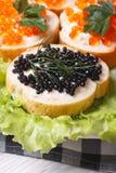 Bocadillos con el caviar rojo y negro en lechuga Imagenes de archivo