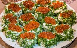 Bocadillos con el caviar rojo y verdes en una placa imagenes de archivo