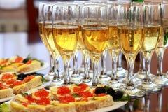 Bocadillos con el caviar y el champán rojos en la tabla Foto de archivo