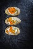 Bocadillos con el huevo y el caviar rojo en tablero de piedra negro Foto de archivo libre de regalías