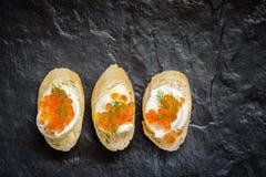 Bocadillos con el huevo y el caviar rojo en tablero de piedra negro Imagen de archivo