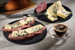 Bocadillos con el queso de Dorblu y la salchicha ahumada cruda en placas negras de la pizarra, un cuchillo del queso y una taza d Imagen de archivo libre de regalías
