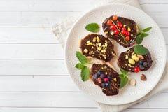 Bocadillos con goma del chocolate, las nueces de pistacho y el berrie fresco imagen de archivo
