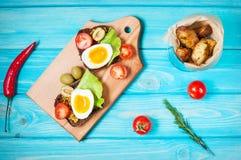 Bocadillos con la aceituna, los huevos de codornices, los tomates de cereza y las patatas en un blueboard de madera Fotos de archivo