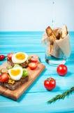 Bocadillos con la aceituna, los huevos de codornices, los tomates de cereza y las patatas en un blueboard de madera Fotografía de archivo