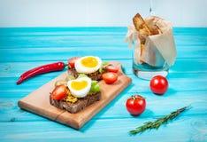 Bocadillos con la aceituna, los huevos de codornices, los tomates de cereza y las patatas en un blueboard de madera Foto de archivo