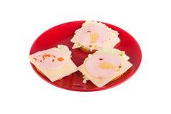 Bocadillos con la salchicha en una placa roja aislada en el fondo blanco Alimento Imagenes de archivo