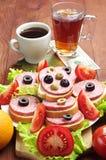 Bocadillos con la salchicha, la taza de café y el té Foto de archivo libre de regalías