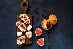 Bocadillos con los higos, el queso de cabra, la miel y los arándanos frescos en el tablero de madera Comida vegetariana, concepto foto de archivo libre de regalías