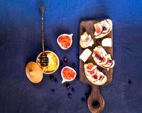 Bocadillos con los higos, el queso de cabra, la miel y los arándanos frescos en el tablero de madera Comida vegetariana, concepto imagen de archivo libre de regalías