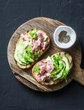 Bocadillos con los pescados del queso cremoso, del aguacate y de atún en tabla de cortar de madera en el fondo oscuro, visión sup Imagen de archivo