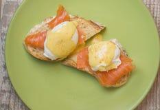 Bocadillos con los pescados rojos, el huevo escalfado y la salsa Foto de archivo