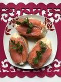 Bocadillos con los salmones, adornados con verdes Mienta en una placa en una servilleta roja Fotos de archivo