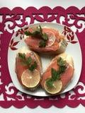 Bocadillos con los salmones, adornados con verdes y el limón Mienta en una placa en una servilleta roja Foto de archivo