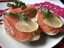 Bocadillos con los salmones, adornados con verdes y el limón Mienta en una placa en una servilleta roja Imagen de archivo libre de regalías