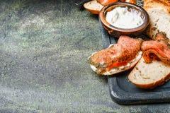 Bocadillos con los salmones y el ricotta en fondo rústico Imágenes de archivo libres de regalías