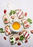 Bocadillos con los salmones y salami, té del perejil y almuerzo en la opinión superior del fondo rústico de madera Imagen de archivo libre de regalías