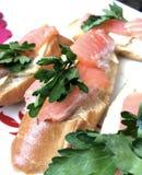 Bocadillos con los salmones y los verdes Los pedazos de pescados se ponen en un baguette del pan, engrasado Adornado con perejil  Foto de archivo