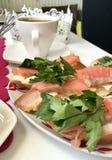 Bocadillos con los salmones y los verdes Los pedazos de pescados se ponen en un baguette del pan, engrasado Adornado con perejil  Imágenes de archivo libres de regalías