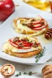Bocadillos de Bruschetta con el brie o queso del camembert, manzanas, nueces, tomillo y miel imagen de archivo