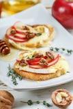 Bocadillos de Bruschetta con el brie o queso del camembert, manzanas, nueces, tomillo y miel fotos de archivo
