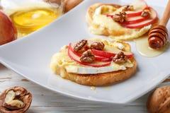 Bocadillos de Bruschetta con el brie o queso del camembert, manzanas, nueces y miel foto de archivo