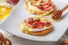Bocadillos de Bruschetta con el brie o queso del camembert, manzanas, nueces y miel fotos de archivo