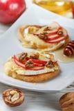 Bocadillos de Bruschetta con el brie o queso del camembert, manzanas, nueces y miel foto de archivo libre de regalías