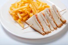 Bocadillos de club con el pollo y patatas fritas en una placa blanca fotos de archivo