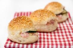 Bocadillos de la hamburguesa en el mantel de la cocina Imagen de archivo libre de regalías