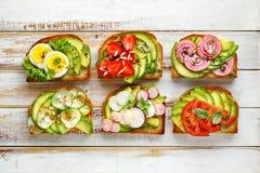 Bocadillos del aguacate, tostadas con los diversos desmoches vegetarianos en una tabla de madera blanca imagen de archivo libre de regalías