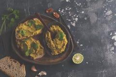 Bocadillos del hummus de los guisantes verdes en un plato oscuro, visión superior, spac de la copia Imágenes de archivo libres de regalías