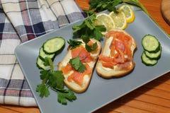 Bocadillos del pan blanco con los pescados y la mantequilla rojos Fotografía de archivo