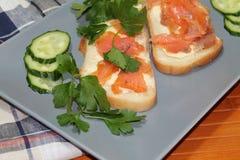 Bocadillos del pan blanco con los pescados y la mantequilla rojos Fotografía de archivo libre de regalías