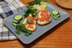 Bocadillos del pan blanco con los pescados y la mantequilla rojos Imagen de archivo libre de regalías