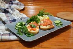 Bocadillos del pan blanco con los pescados y la mantequilla rojos Fotos de archivo